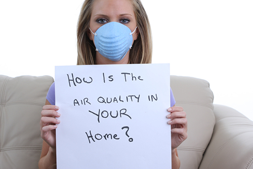 Gril wearing dust mask and holding paper with a question about air quality.