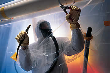 Asbestos Removal: Technician wearing protective gear and removing asbestos.